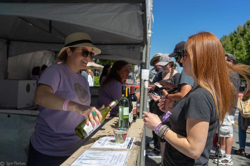 chamber volunteer pouring wine